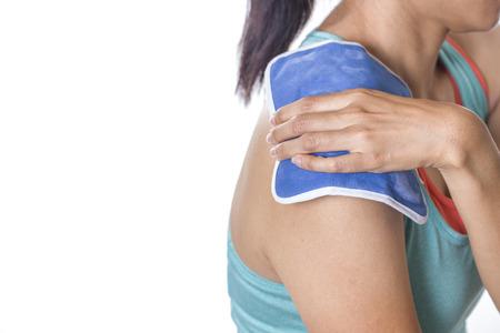 dolor  muscular: mujer que pone una bolsa de hielo sobre su dolor en el hombro Foto de archivo