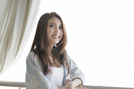 Beautiful asian woman standing among morning sunshine 写真素材