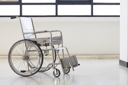 disablement: Empty wheelchair parked in hospital hallway
