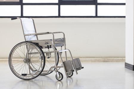 a hospital: Empty wheelchair parked in hospital hallway