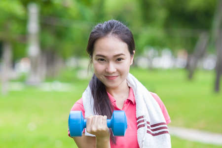front raise: Fitness woman lifting dumbbell weight training outside