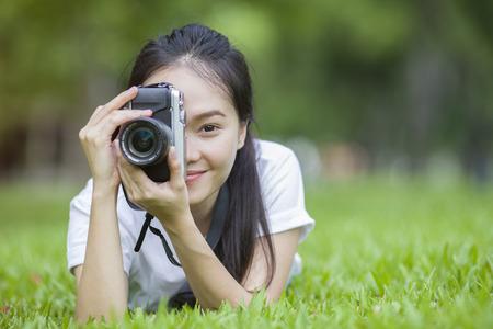 カメラで女の子が草に寝転んで