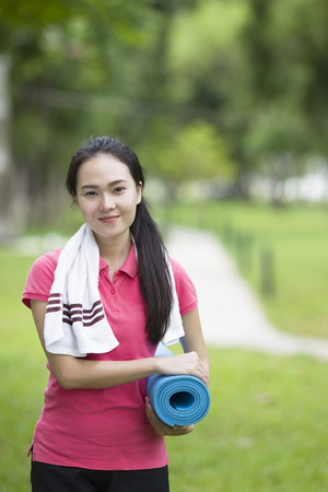 asian adult: Young woman holding a yoga mat Stock Photo