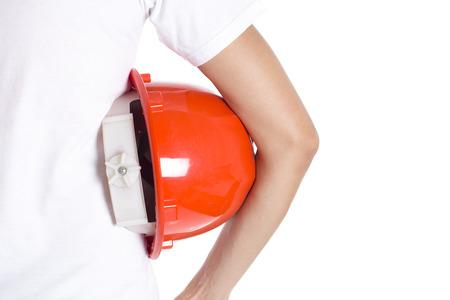 casco rojo: mano femenina ingeniero celebración de casco rojo sobre fondo blanco