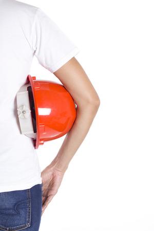 casco rojo: female engineer hand holding red helmet on white background Foto de archivo