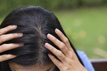 젊은 여자는 그녀의 회색 머리의 뿌리를 보여줍니다