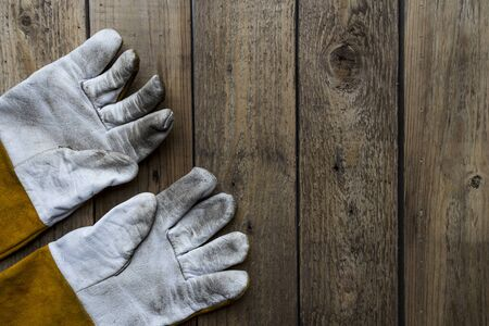 work gloves: old dirty leather work gloves on wood background