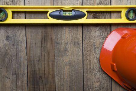 casco rojo: Nivel del edificio amarillo y casco rojo sobre la mesa de madera vieja Foto de archivo