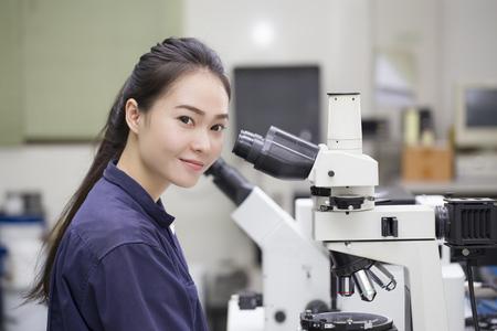 研究室では研究室の顕微鏡顕微鏡で探していた女性科学者 写真素材
