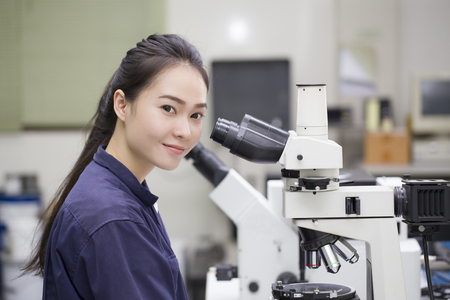 bata de laboratorio: Cient�fico de sexo femenino que mira en microscopio en el laboratorio Microscopio de laboratorio Foto de archivo