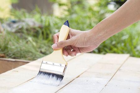 pintor de casas: trabajador de la mano que sostiene la pintura pincel blanco sobre textura de madera