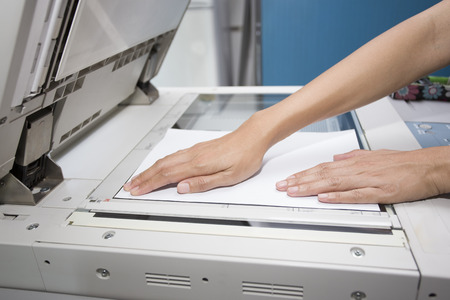 copying: woman hands putting a sheet of paper into a copying device Stock Photo