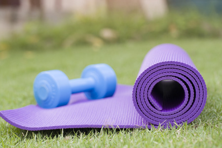 four classes: purple yoga mat and blue dumbbell Stock Photo