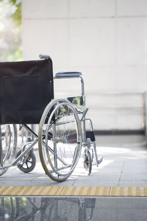 healthcare facility: Empty wheelchair parked in hospital Stock Photo