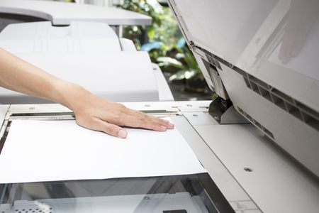 woman hands putting a sheet of paper into a copying device Standard-Bild
