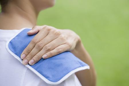 douleur epaule: femme de mettre un sac de glace sur sa douleur à l'épaule