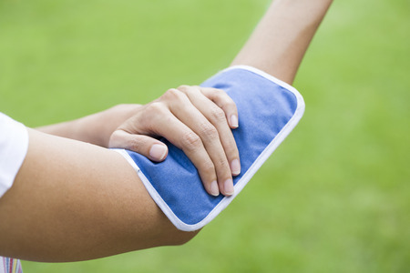 pained: woman putting an ice pack on her arm pain