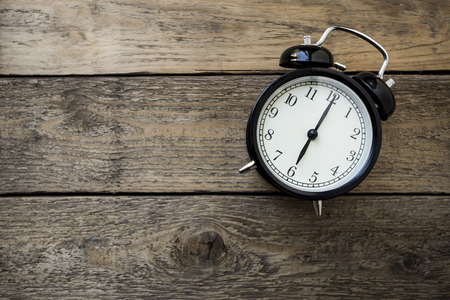 time zone: Retro alarm clock on wooden table