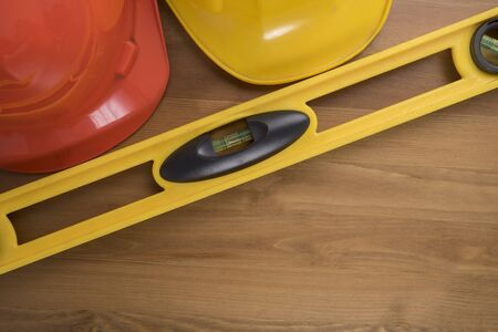 leveler: Yellow building level and helmets on the old wood table