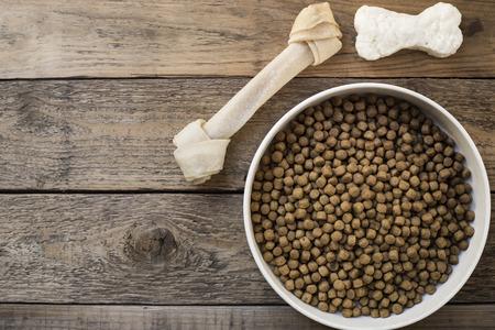 treats: hueso de perro y comida para perros en la mesa de madera Foto de archivo