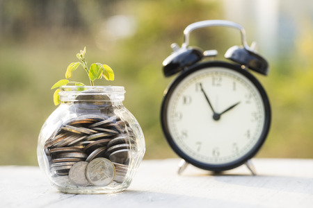 banco dinero: Sprout growing on glass bottle bank with alarm clock, saving money concept