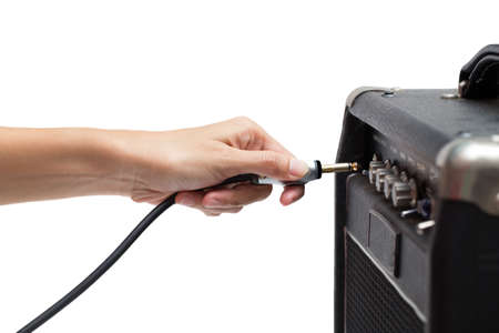 unplugging: woman hand plugging into the amplifier guitar on white background