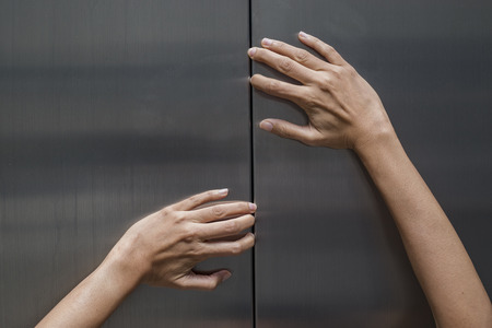 ghost woman: woman hands try to stop doors of the closed elevator