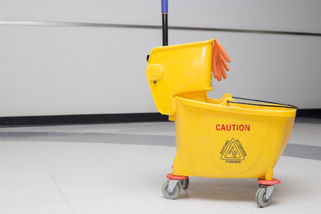 mopped: Yellow mop bucket and set of cleaning equipment in the office