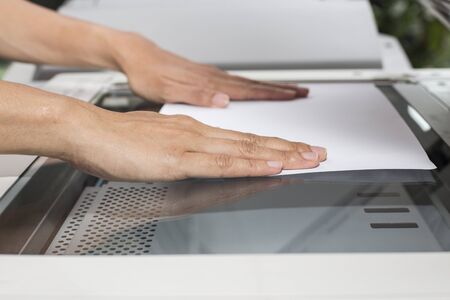 xerox: woman hands putting a sheet of paper into a copying device Stock Photo