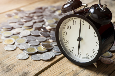 minute hand: time and money on wood table, concept and idea