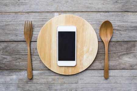 food absorption: mobile phone served on wood plate. Concept and idea