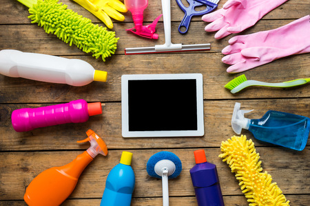 office cleanup: House cleaning product and tablet on the table