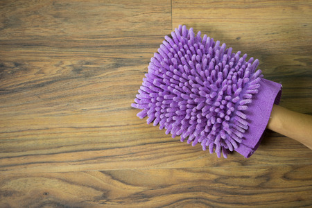 hand wear: Hand wear violet fabric hand wash glove on wood table background