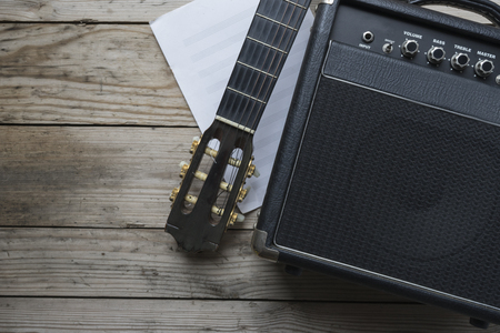 concert background: Guitar amplifier and guitar on wood table