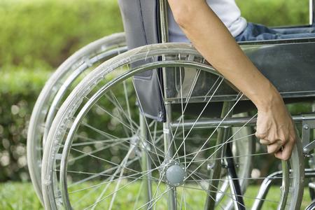 donna, usando una sedia a rotelle in un parco Archivio Fotografico
