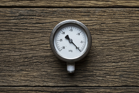metering: pressure gauge on wood background