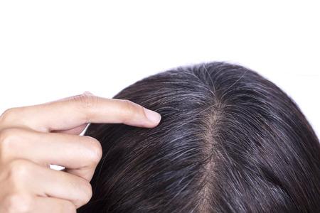 Junge Frau zeigt ihre grauen Haarwurzeln Standard-Bild