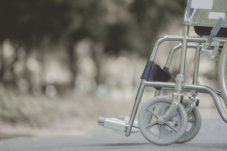 healthcare facility: Empty wheelchair parked in park, retro filter effect