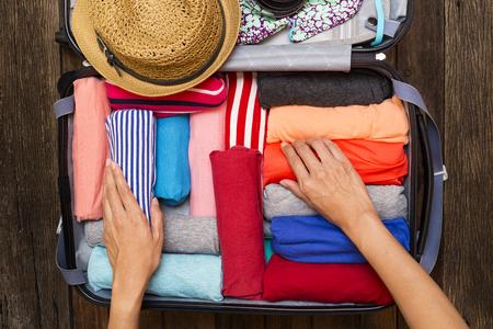Donna imballaggio un bagaglio per un nuovo viaggio Archivio Fotografico - 65397334