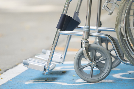 Pavement handicap symbol and wheelchair Stock Photo