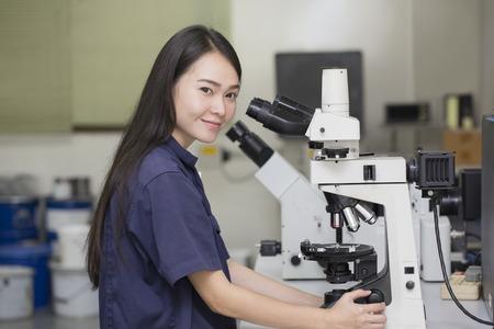 femme scientifique regardant dans un microscope dans le laboratoire microscope Banque d'images