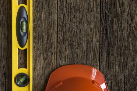 casco rojo: nivel del edificio amarillo y casco rojo sobre la mesa de madera