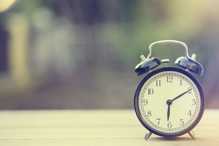 Retro alarm clock on wooden table, vintage style