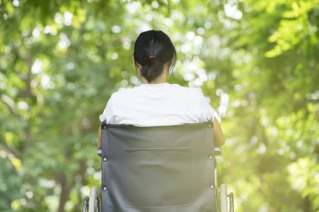 vrouw met behulp van een rolstoel in een park