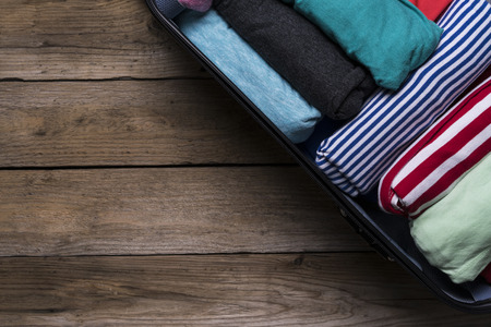 open suitcase: Open suitcase with clothing on wood table