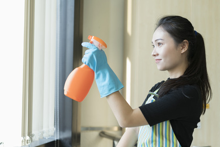 happy woman in gloves cleaning window with cleanser spray at home