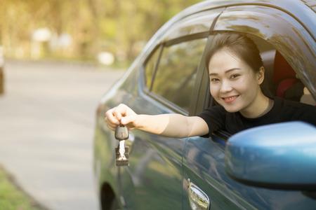 jonge tevreden vrouw in auto met zonlicht Stockfoto