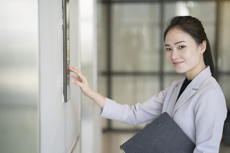 businesswoman pressing elevator up button in the office
