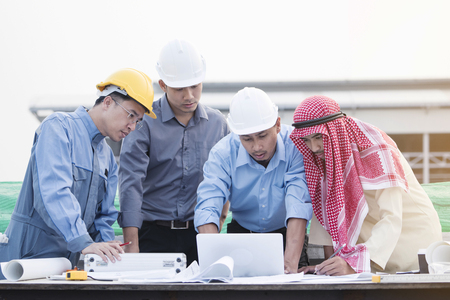 consulted: Asian engineers were consulted together and plan in construction site Stock Photo