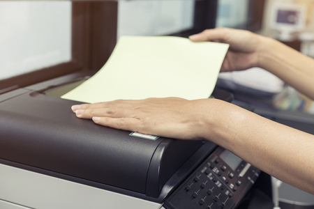 woman hands putting a sheet of paper into a copying device 版權商用圖片